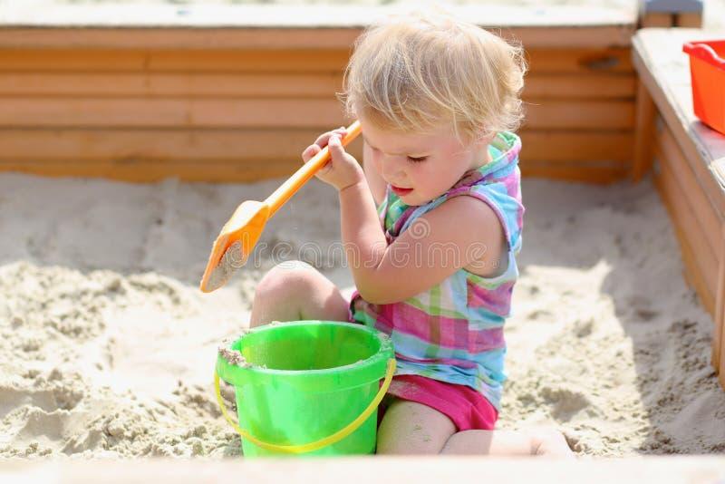 Weinig leuk meisje die in zandbak spelen stock foto