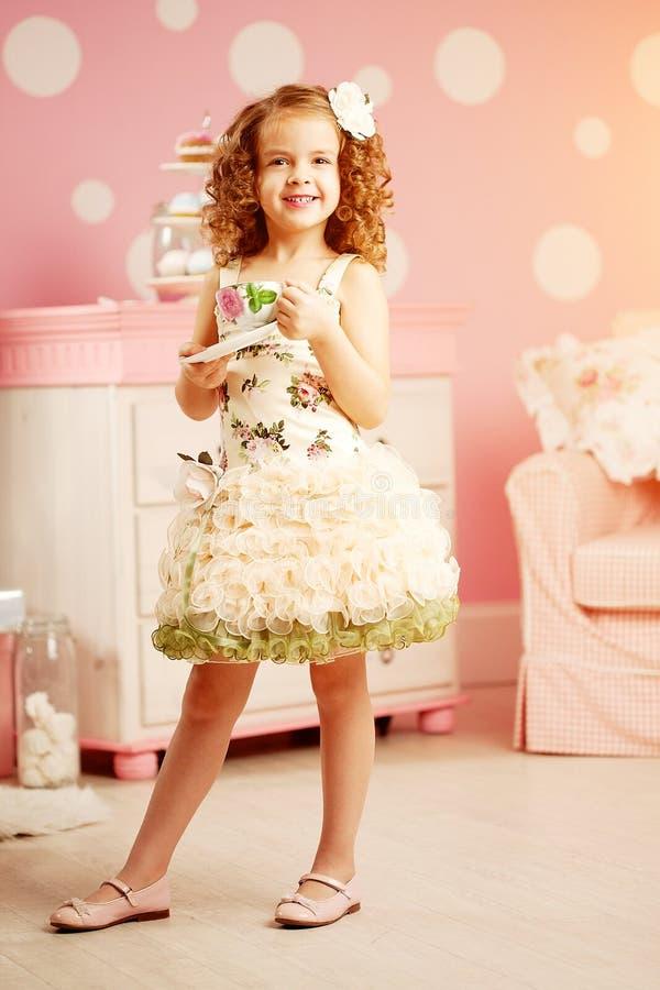 Weinig leuk meisje in een roze kleding drinkt thee met snoepjes in c royalty-vrije stock foto's