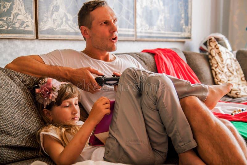 Weinig leuk meisje gebruikt tablet, speelt haar vader console royalty-vrije stock afbeelding