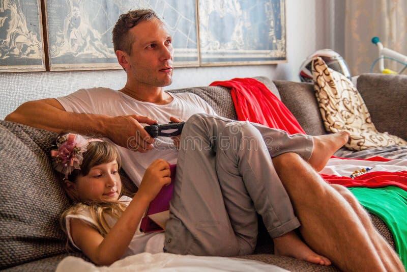 Weinig leuk meisje gebruikt tablet, speelt haar vader console stock foto's