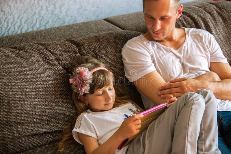 Weinig leuk meisje gebruikt tablet, speelt haar vader console royalty-vrije stock foto's