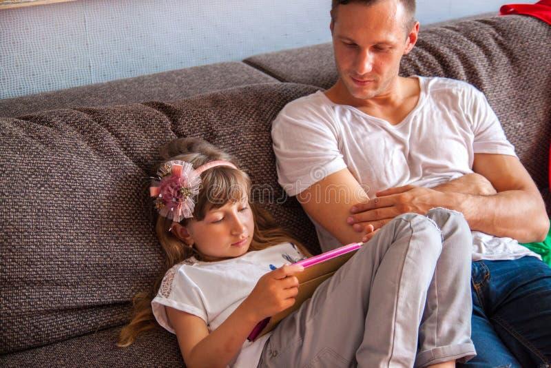 Weinig leuk meisje gebruikt tablet, speelt haar vader console stock fotografie