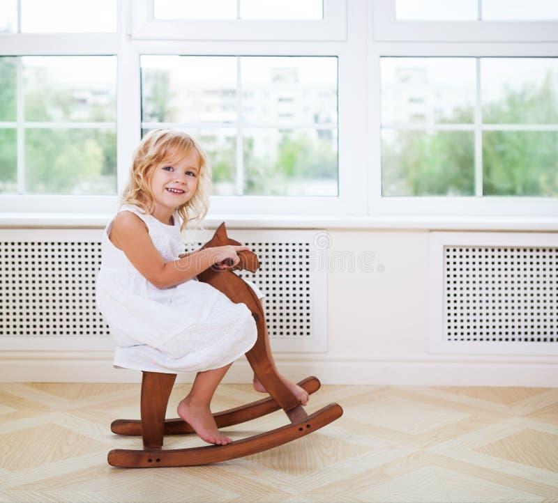 Weinig leuk meisje in kinderdagverblijfruimte met houten paard stock fotografie