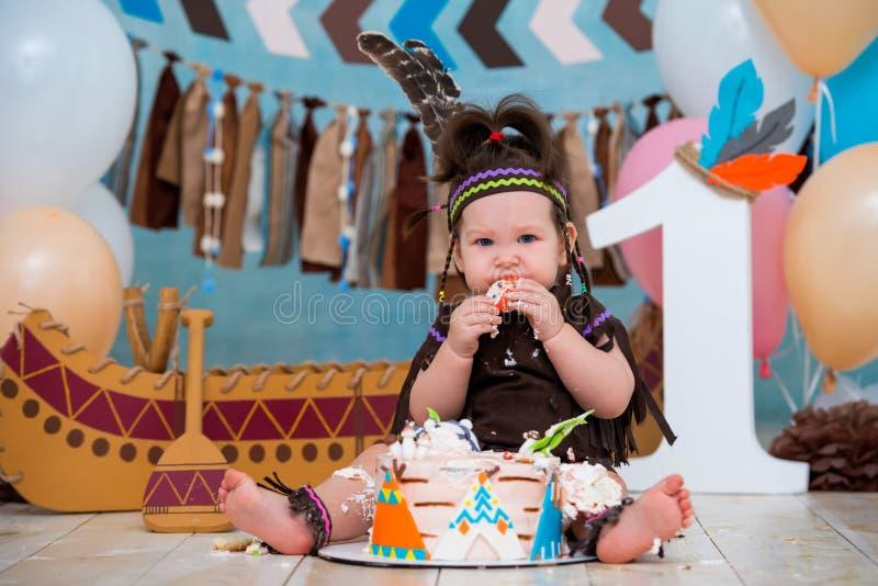 Weinig leuk meisje in kostuum van de Indische leider van Apache en in een veerhoofddeksel zit en proeft een zoete cake Eerste ver royalty-vrije stock afbeelding
