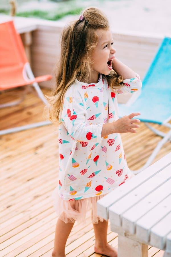 Weinig leuk meisje met zeeschelp in handen bij tropisch strand royalty-vrije stock foto