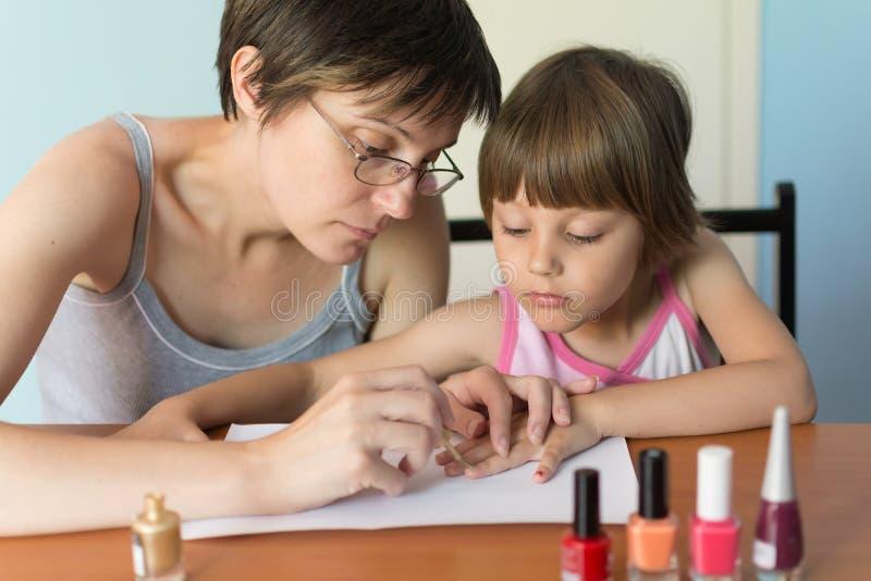 Weinig leuk meisje schildert spijkers royalty-vrije stock afbeeldingen