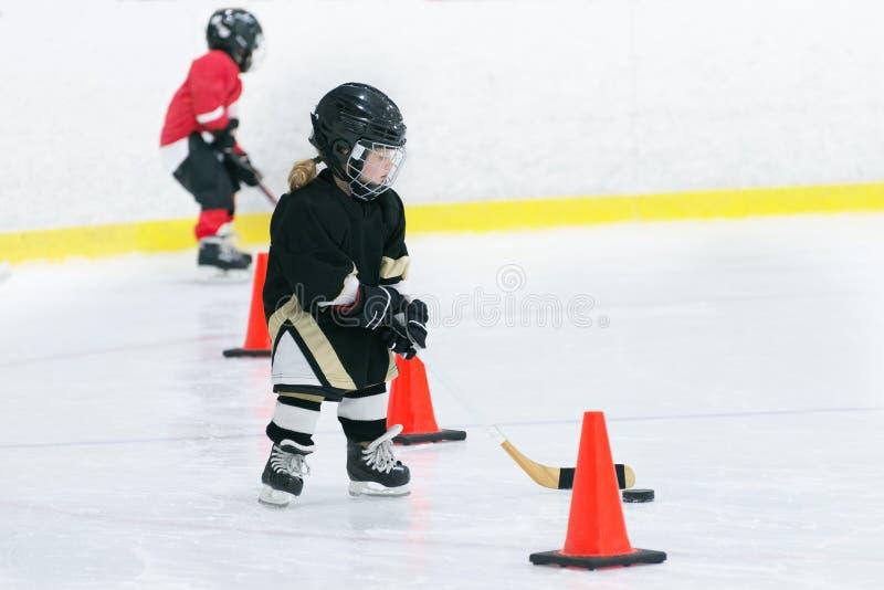 Weinig leuk meisje speelt hockey op ijs die in volledig hockeymateriaal dragen Zij doet trainingen met een stok en een puck stock afbeelding