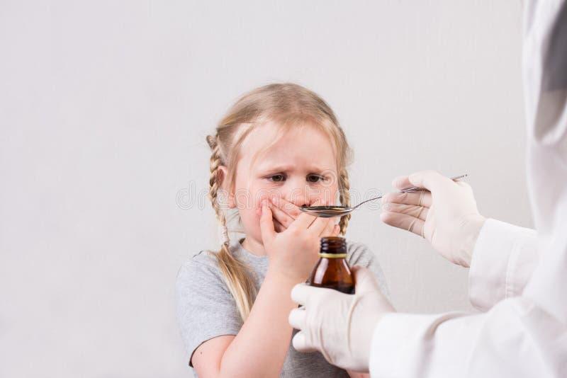Weinig leuk meisje trekt ` t wil aan krijgt lepel van geneeskunde vloeibare het drinken stroop stock foto
