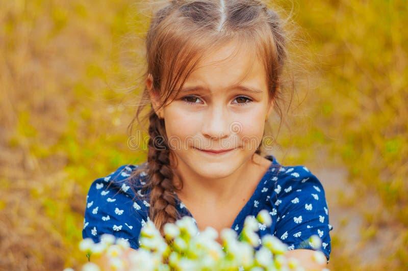 Weinig leuk meisje verzamelt een boeket van wilde bloemen op een de zomerdag op het gebied stock foto's