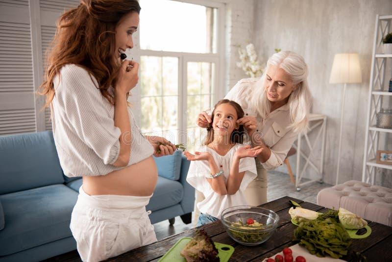 Weinig leuk prettig meisje die zoete kers met mamma en grootmoeder eten royalty-vrije stock afbeeldingen