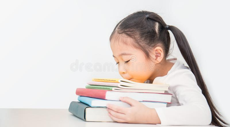 Weinig leuke Aziatische meisjesslaap op stapel boeken probeerde van school stock fotografie