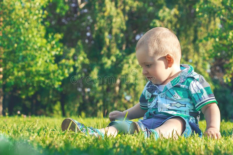 Weinig leuke baby die in het gras situeren Levensstijl, Manier en in stijl Adverterende kleren De zomerinzameling stock afbeelding