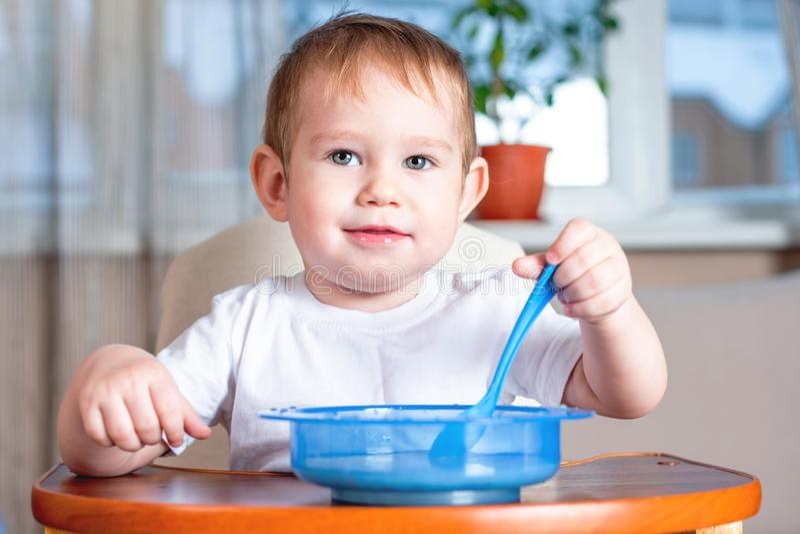 Weinig leuke baby die met een lepel zelf bij de jonge geitjes leren te eten dient in de keuken in Gezonde babyvoeding stock foto's