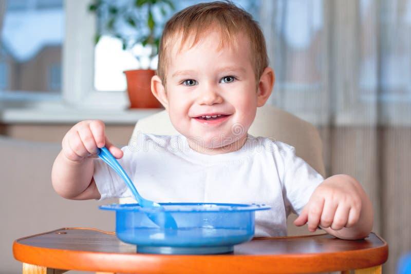 Weinig leuke baby die met een lepel zelf bij de jonge geitjes leren te eten dient in de keuken in Gezonde babyvoeding royalty-vrije stock afbeeldingen
