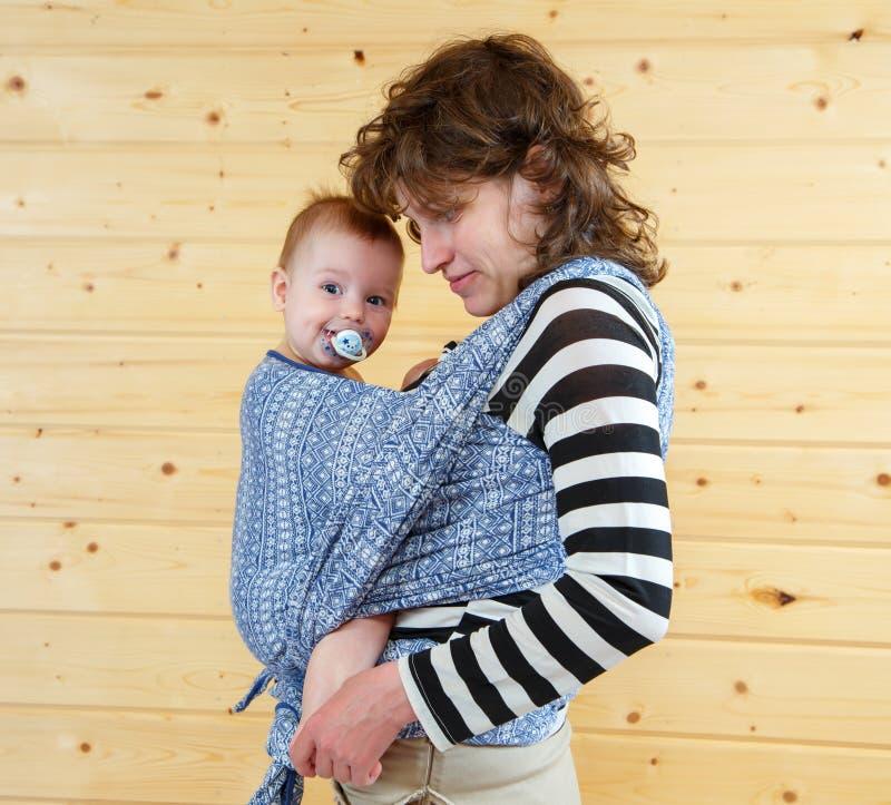 Weinig leuke baby met soother in het dragen van slinger stock foto