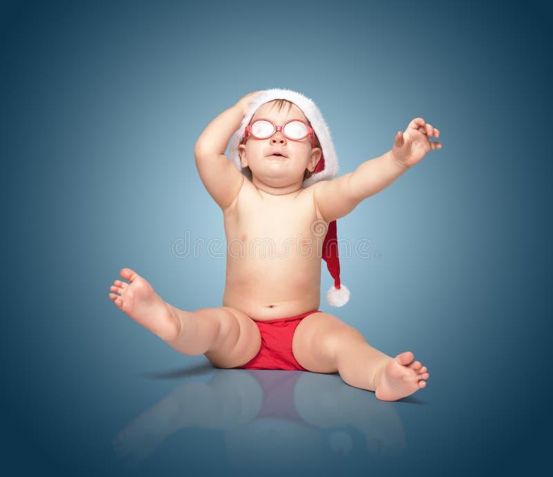 Weinig leuke baby in rode Kerstmanhoed en rode glazen royalty-vrije stock afbeelding