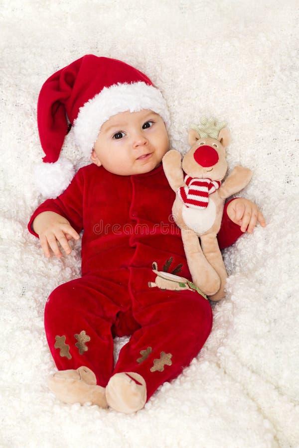 Weinig leuke babyjongen, kleedde zich globaal in rood met santahoed stock fotografie