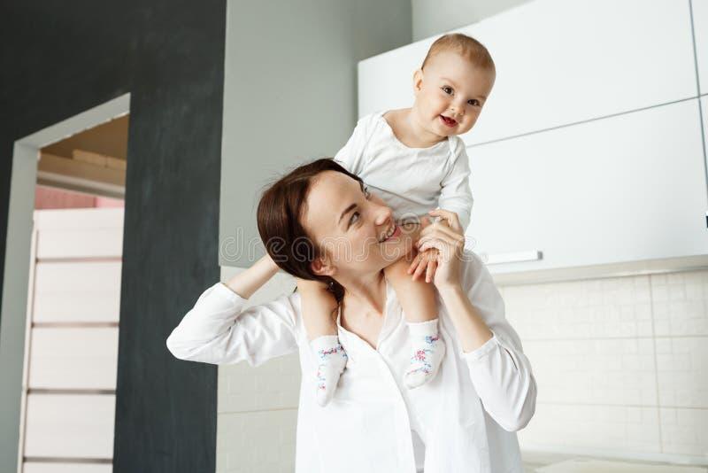 Weinig leuke babyjongen met grote bruine ogen die op moederhals zitten en gelukkig glimlachen Moederholding hem met handen royalty-vrije stock afbeeldingen