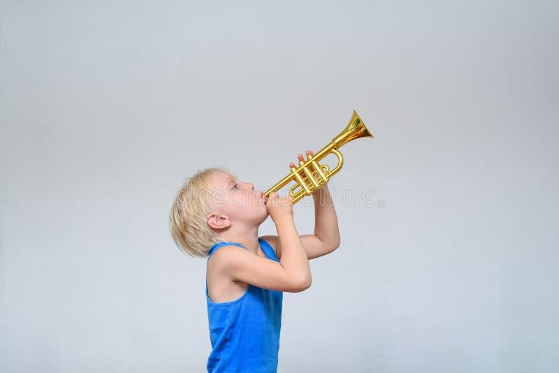 Weinig leuke blonde jongen het spelen stuk speelgoed trompet op lichte achtergrond royalty-vrije stock afbeeldingen