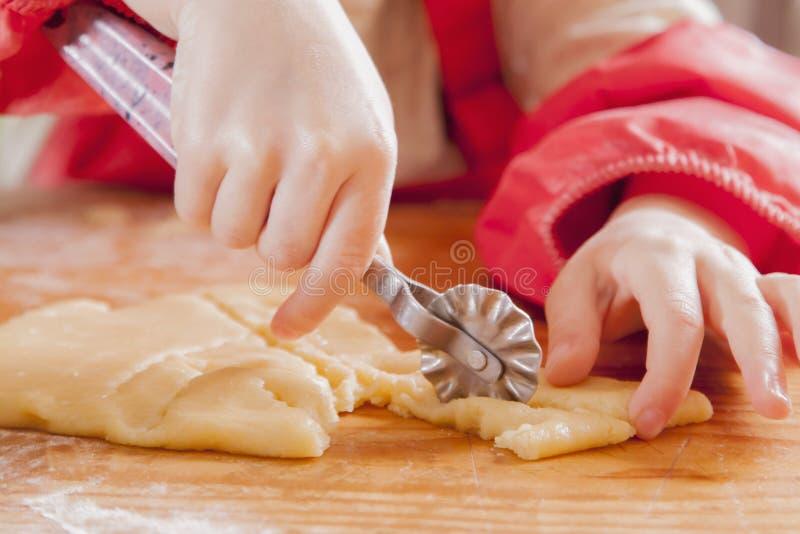 Weinig leuke chef-kok van het kindmeisje snijdt het deeg en het maken van met de hand gemaakte cakes Voedsel, ?ooking proces, sno royalty-vrije stock afbeeldingen