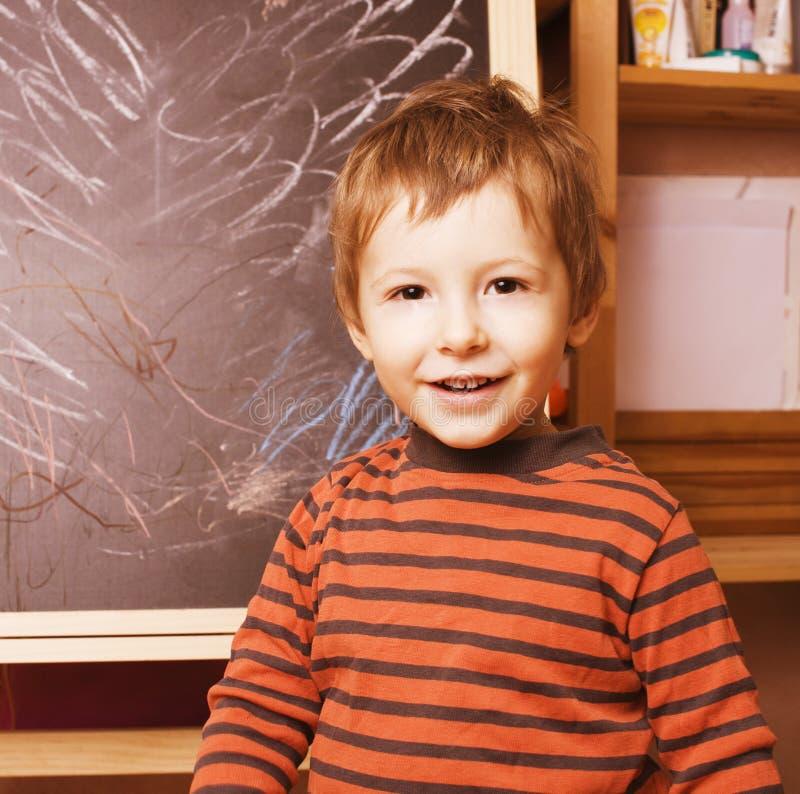 Weinig leuke echte jongen bij bord in klaslokaal, terug naar school het schilderen royalty-vrije stock afbeelding