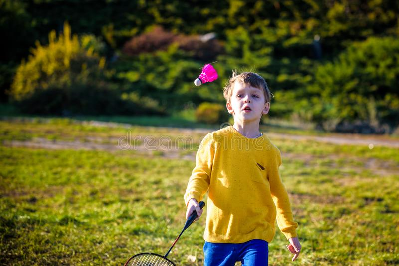 Weinig leuke grappige jong geitjejongen met badmintonracket het spelen in park op de warme dag van de de zomerlente Actieve in op stock afbeeldingen