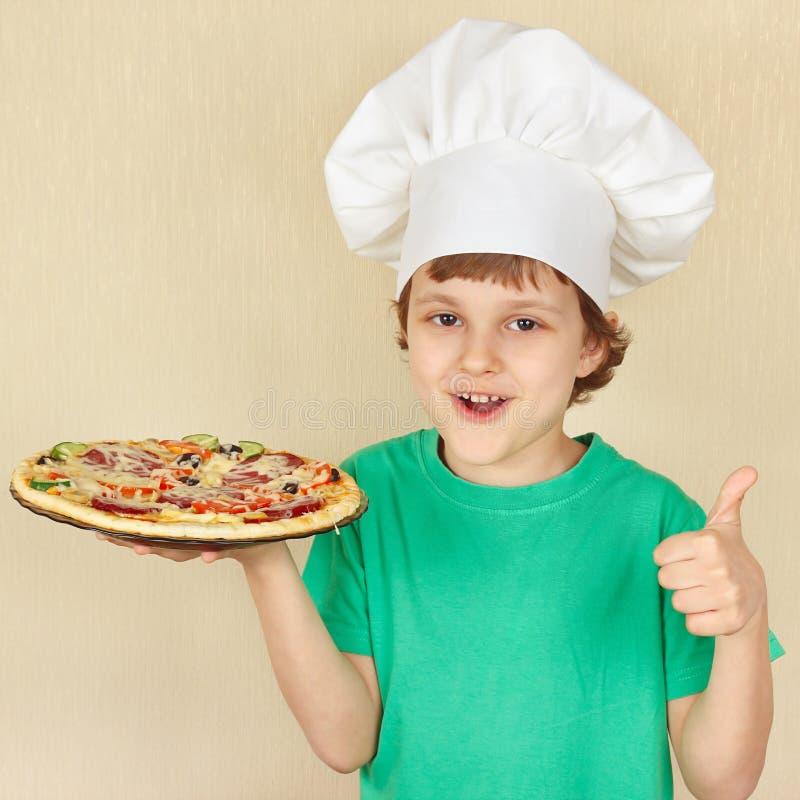 Weinig leuke jongen in chef-kokshoed met gekookte smakelijke pizza stock foto