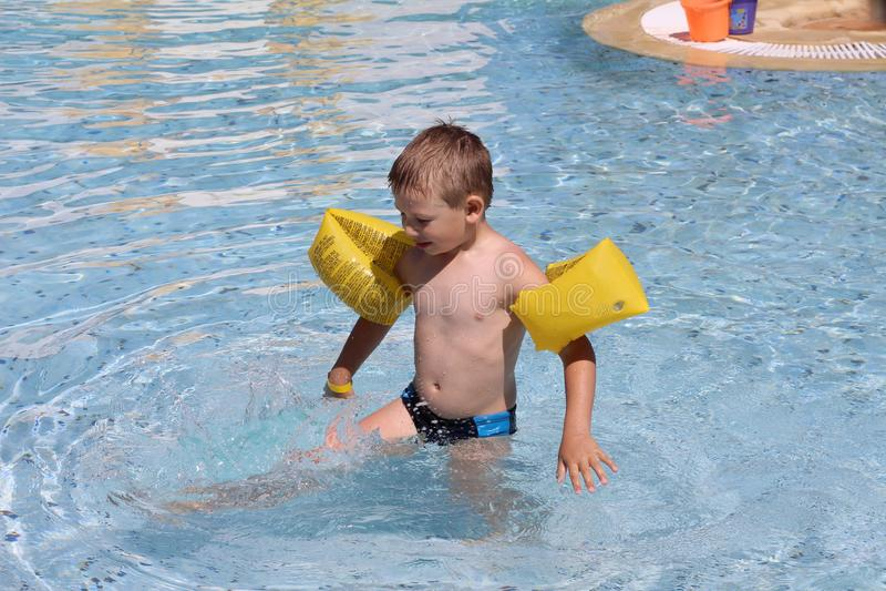Weinig leuke jongen in de zomer zwemt in de pool royalty-vrije stock foto's