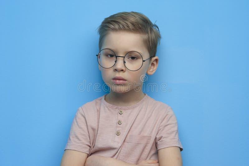 Weinig leuke jongen in glazen die zorgvuldig stellen stock afbeeldingen