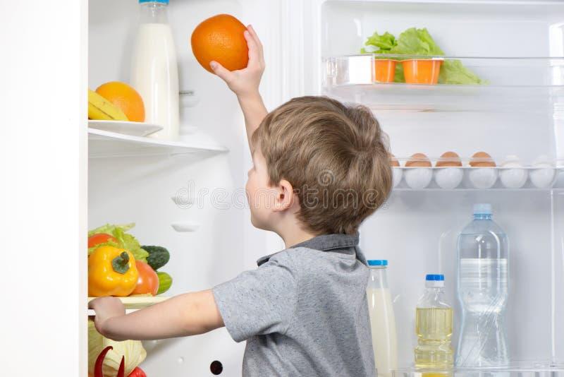 Weinig leuke jongen het plukken sinaasappel van koelkast royalty-vrije stock foto's