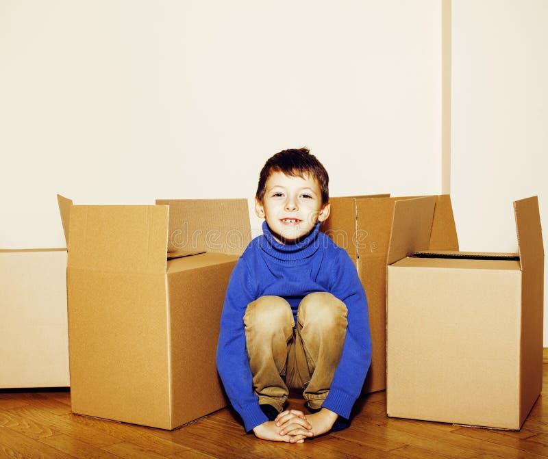 Weinig leuke jongen in lege ruimte, beweging aan nieuw huis het huis alleen onder dozen sluit omhoog jong geitje glimlachend, lev stock foto's