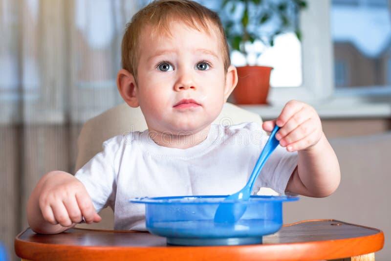 Weinig leuke jongen met een lepel leren te eten zelf die in de keuken Concept gezond babyvoedsel royalty-vrije stock fotografie