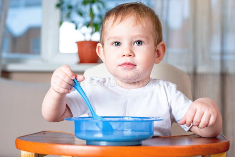 Weinig leuke jongen met een lepel leren te eten zelf die in de keuken Concept gezond babyvoedsel stock fotografie