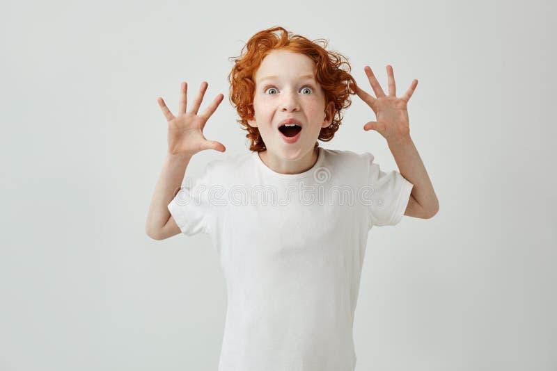 Weinig leuke jongen met gemberhaar in witte t-shirt die pret hebben die thuis, ogen met geopende mond knallen wanneer de moeder p royalty-vrije stock fotografie