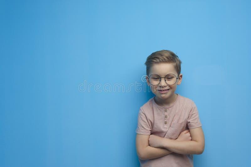 Weinig leuke jongen met glazen die op een blauwe achtergrond stellen stock afbeelding