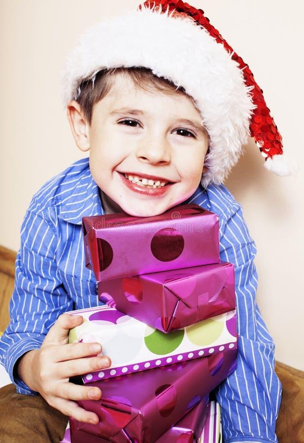Weinig leuke jongen met Kerstmisgiften thuis sluit omhoog emotioneel stock foto