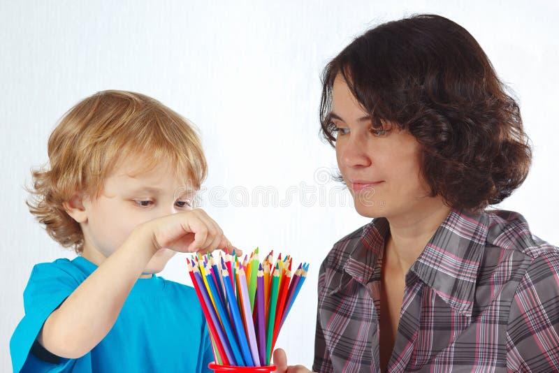 Weinig leuke jongen met zijn moeder kijkt op kleurenpotloden royalty-vrije stock foto's