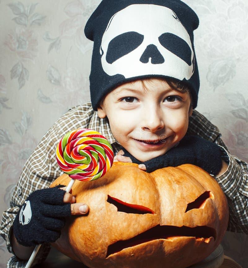 Weinig leuke jongen in skelethoed met pompoen en suikergoed bij Halloween-partijvakantie, het concept van levensstijlmensen royalty-vrije stock foto