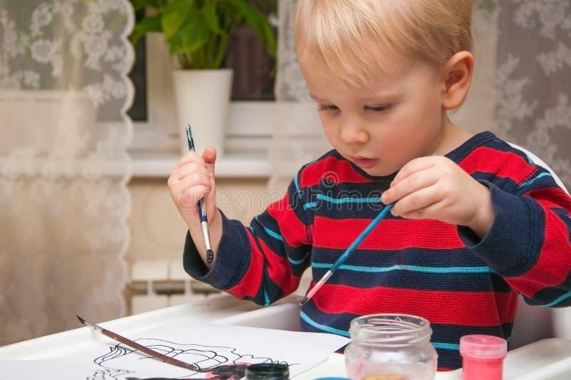 Weinig leuke jongen trekt verven en vingers royalty-vrije stock fotografie