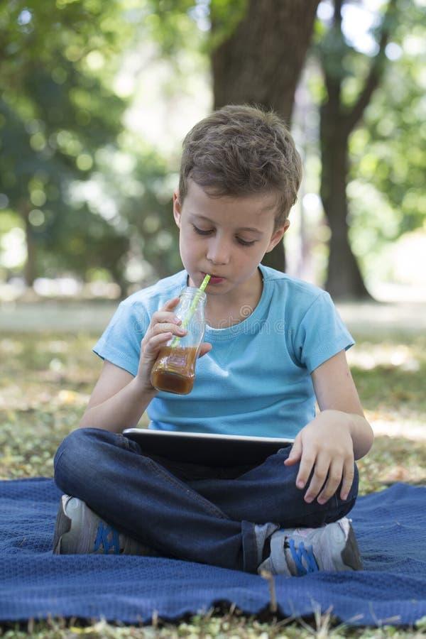 Weinig leuke jongen van pre-school leeftijd gebruikt een digitale tablet royalty-vrije stock afbeeldingen