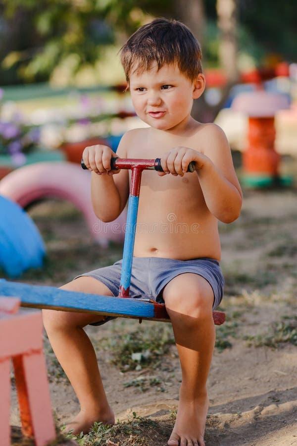 Weinig leuke jongen zonder een overhemd speelt op de Speelplaats royalty-vrije stock foto