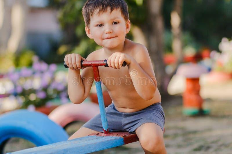 Weinig leuke jongen zonder overhemd spelen die op de Speelplaats, een houten schommeling berijden stock afbeeldingen