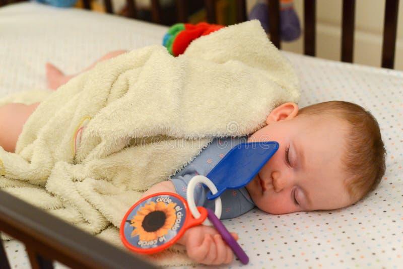 Weinig leuke Kaukasische baby slaapt in de voederbak De zuigeling houdt stuk speelgoed royalty-vrije stock foto's