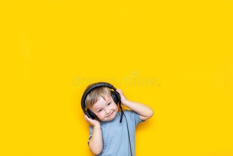 Weinig leuke Kaukasische blondejongen in hoofdtelefoons die het gelukkige glimlachen op gele achtergrond stellen stock foto