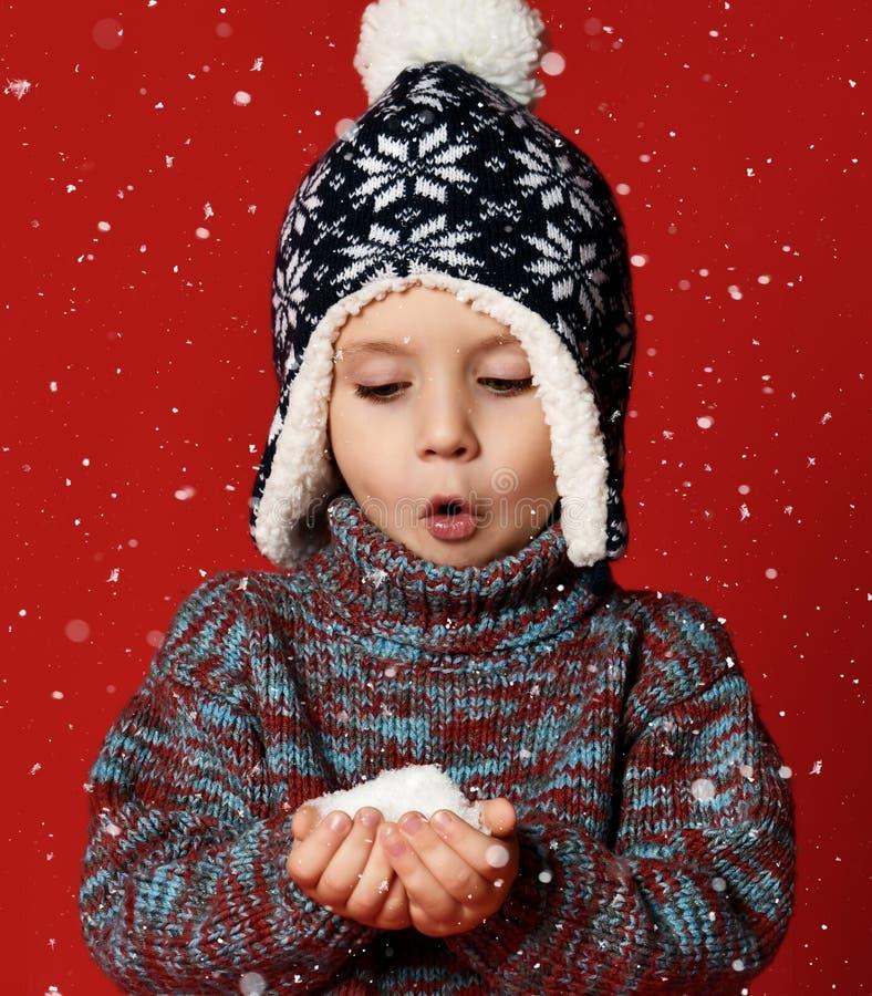 Weinig leuke kindjongen houdt sneeuw in handen die warme die kleren dragen en hoed op rode achtergrond wordt geïsoleerd stock afbeeldingen