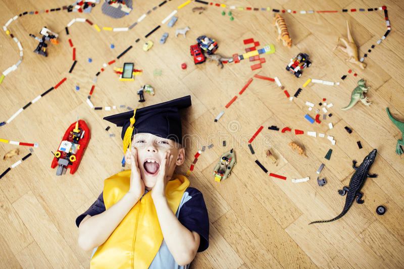 Weinig leuke kleuterjongen onder speelgoedlego thuis in het gediplomeerde hoed het glimlachen emotioneel stellen, het concept van stock fotografie