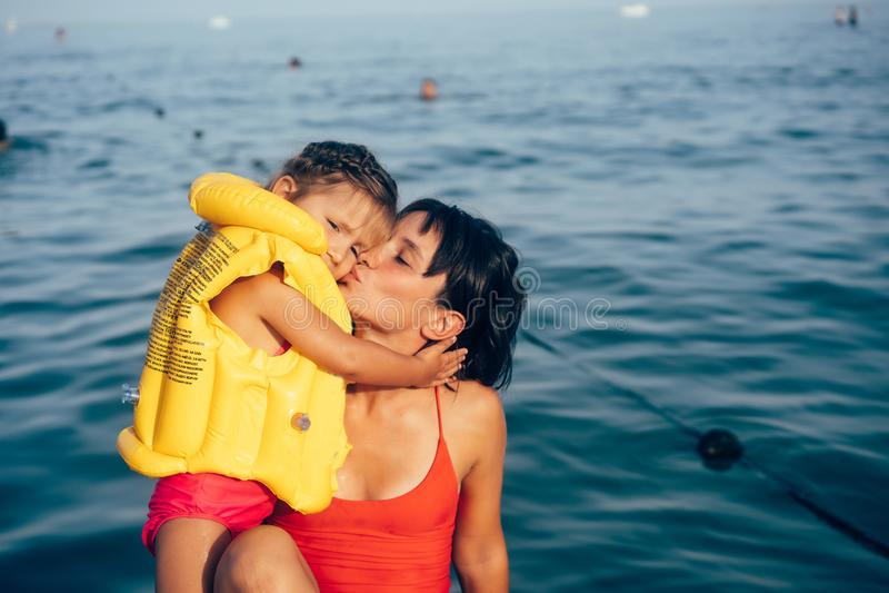 Weinig leuke meisjesbaby en jonge moeder bij strand stock foto's