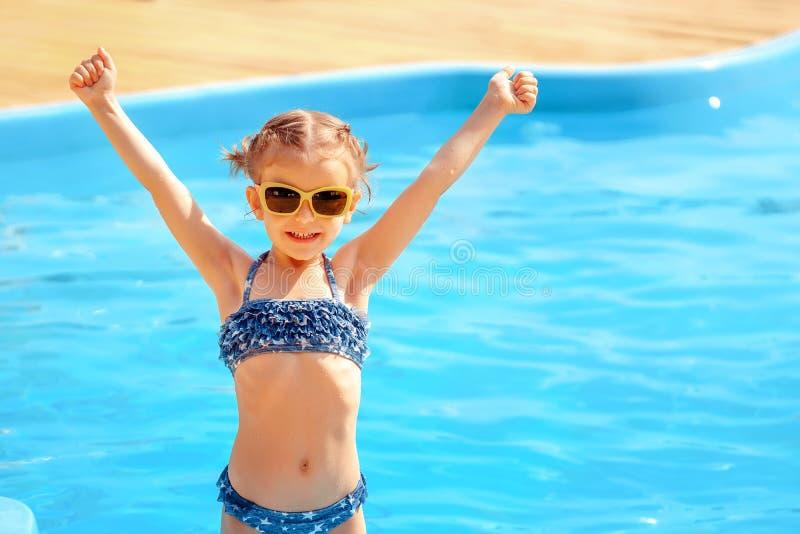 Weinig leuke meisjesholding overhandigt op dichtbij een zwembad stock foto's