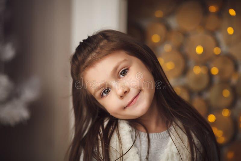 weinig leuke meisjeszitting dichtbij Kerstmisboom en open haard royalty-vrije stock foto's