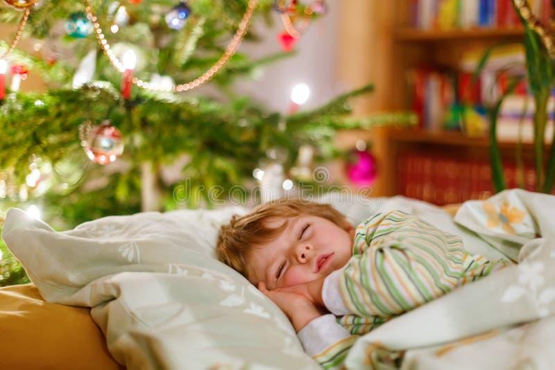 Weinig leuke slaap van de jong geitjejongen onder Kerstboom royalty-vrije stock foto's